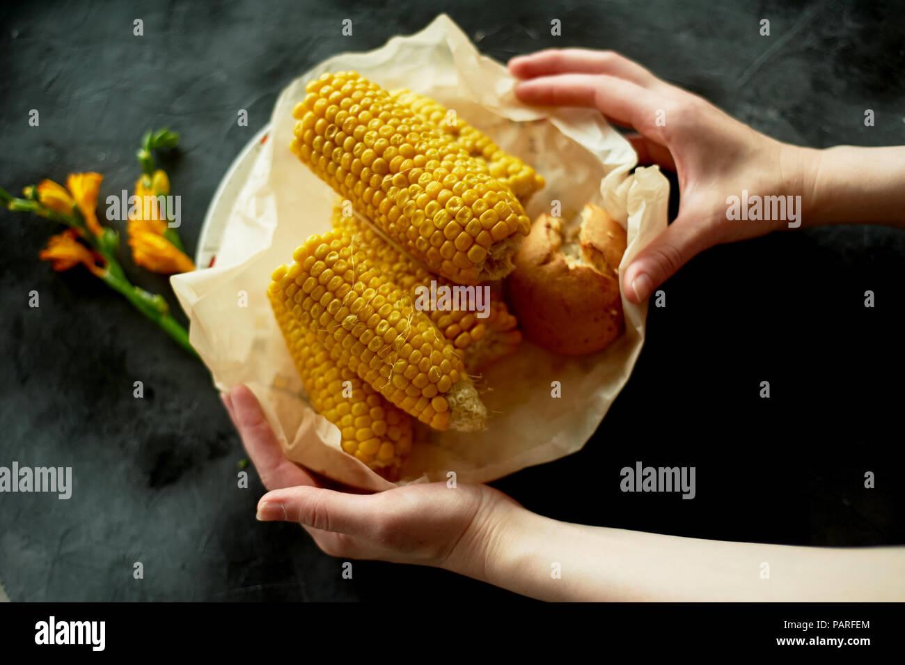 Eine Platte mit gekochte Maiskolben, auf Pergamentpapier, in einen Teller. Auf einem dunklen Hintergrund, im rustikalen Stil. Vegetarische einfaches Essen Stockbild