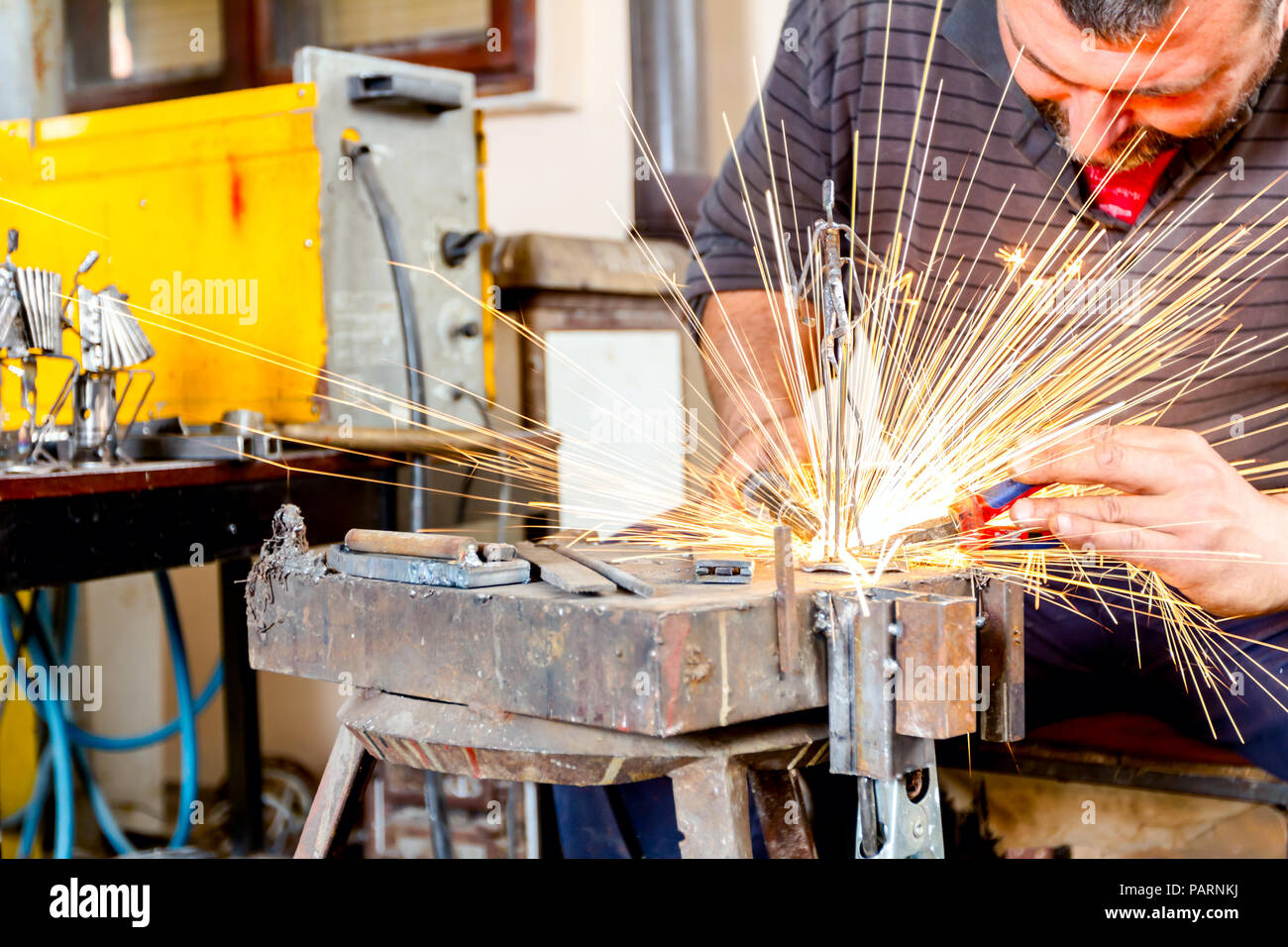 Bildhauer ist unter Verwendung des arc-Schweißen Montage Metall Skulptur ohne angemessenen Schutz, Barehanded. Stockbild
