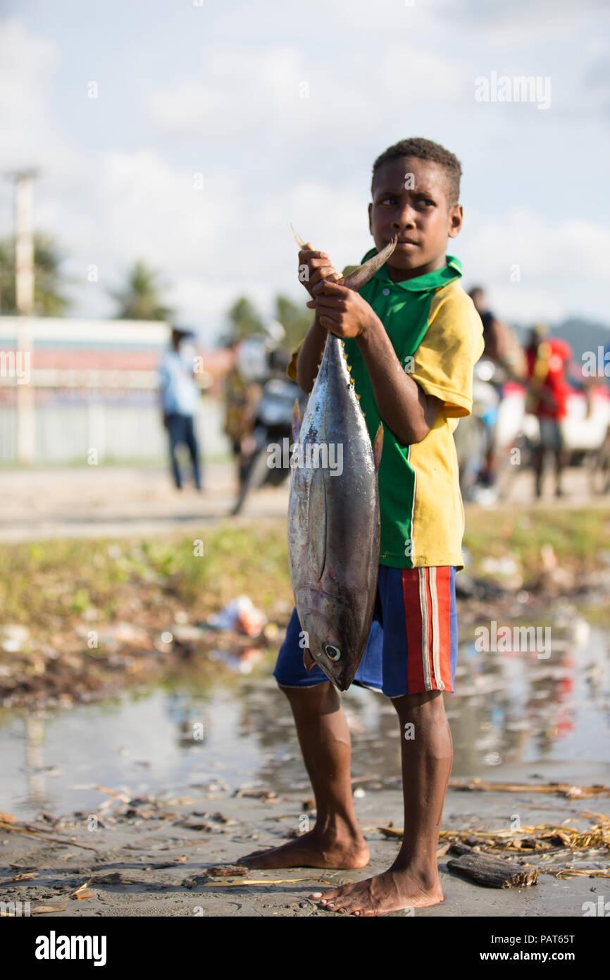 Papua-Neu-Guinea, Vanimo, junge im Dorf, mit großen Fischen. Stockbild