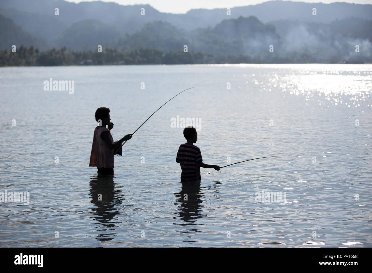 Papua Neu Guinea, Vanimo, Silhouette von Mutter und Kind im Wasser Angeln. Stockbild