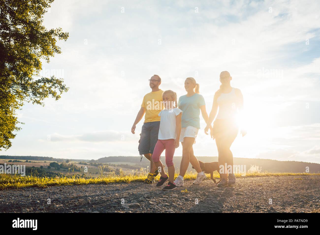 Familie in einem abendlichen Spaziergang mit dem Hund Stockbild