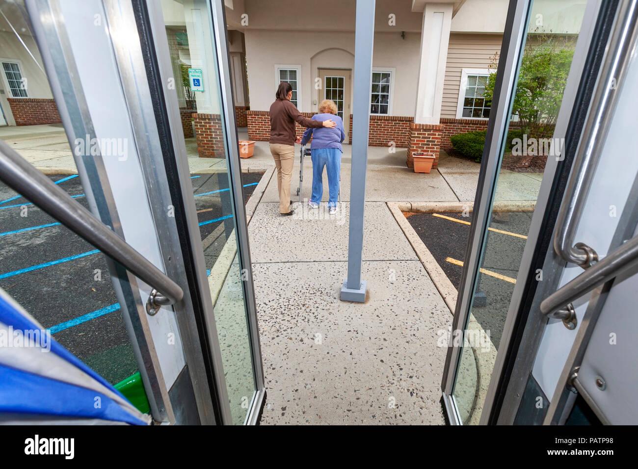 Eine Sozialarbeiterin unterstützt eine Seniorin Frau mit einem Walker ein Erwachsener Tagesstätte für ältere Menschen zu nähern. Stockbild