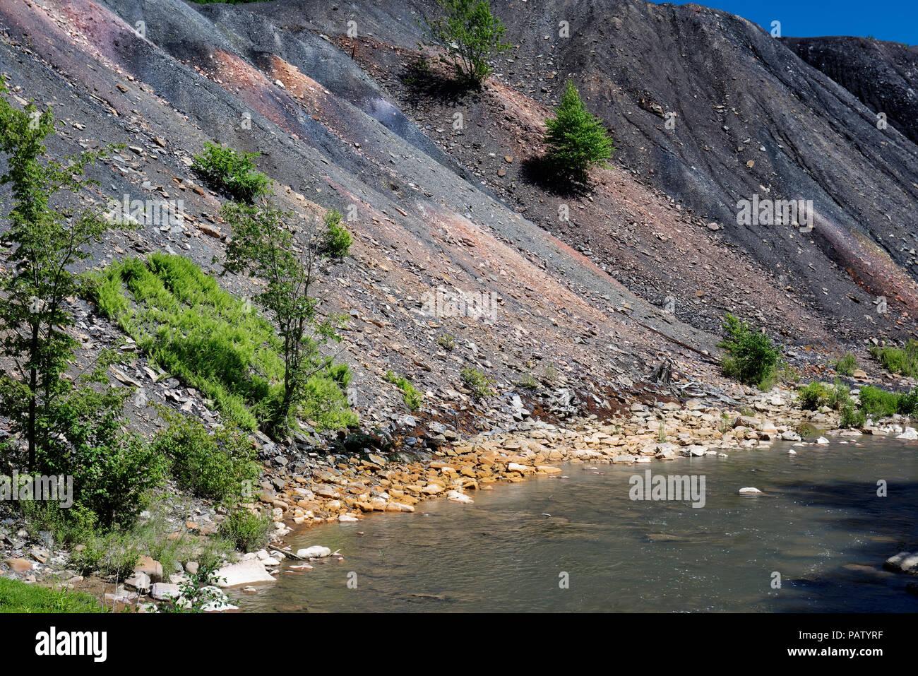 Kohle Grube Rückstände Abfälle verwöhnen Stapel neben einem Bach mit orangefarbenen Felsen, Umweltschäden durch giftige Verunreinigung und Acid Mine Drainage. Stockbild