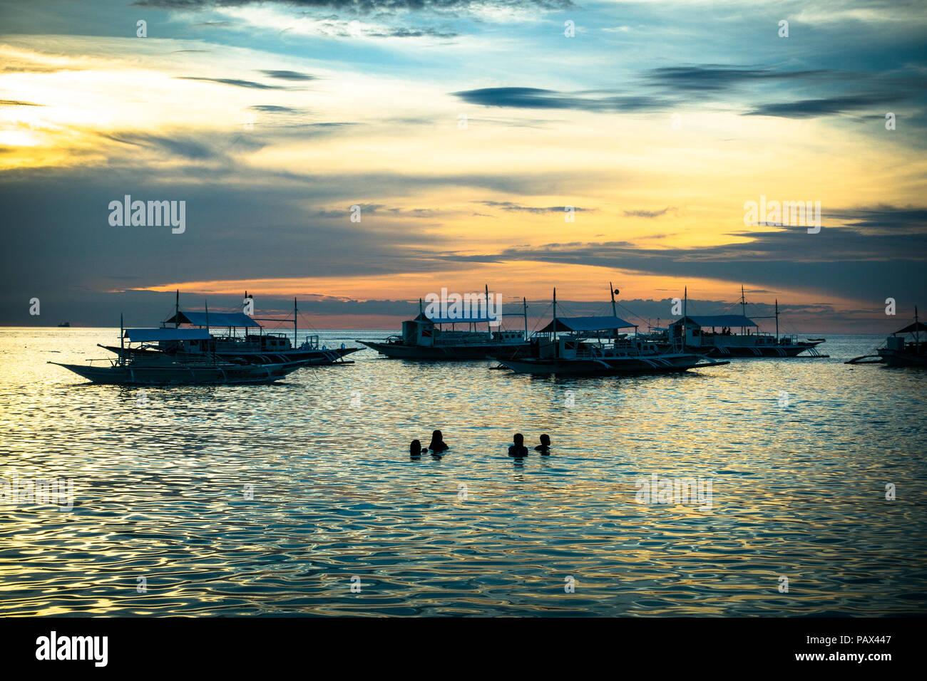 Silhouette von vier Touristen Schwimmen und Spielen im Meer in der Nähe von Fischerboote bei Sonnenuntergang - Malapascua - Philippinen, Cebu Stockbild