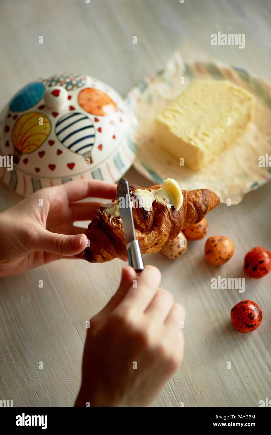 Licht ästhetische französisches Frühstück. Das Mädchen ist Zustimmen ein Croissant mit Butter. Im Rahmen der Hand Stockbild
