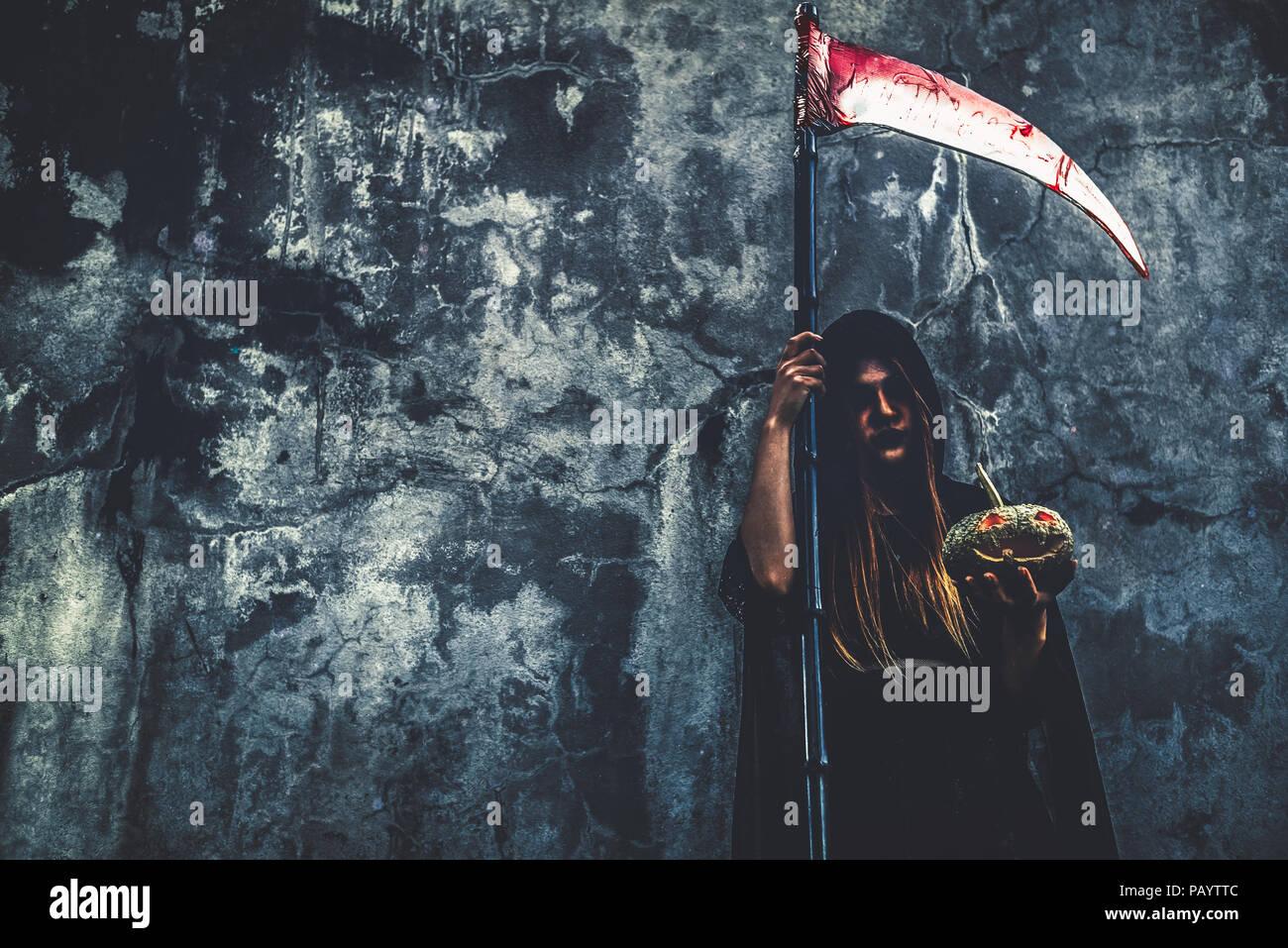 Daemon Hexe mit reaper auf grunge Wand Hintergrund. Halloween und religiöses Konzept. Daemon Engel und Satan Thema. Stockbild