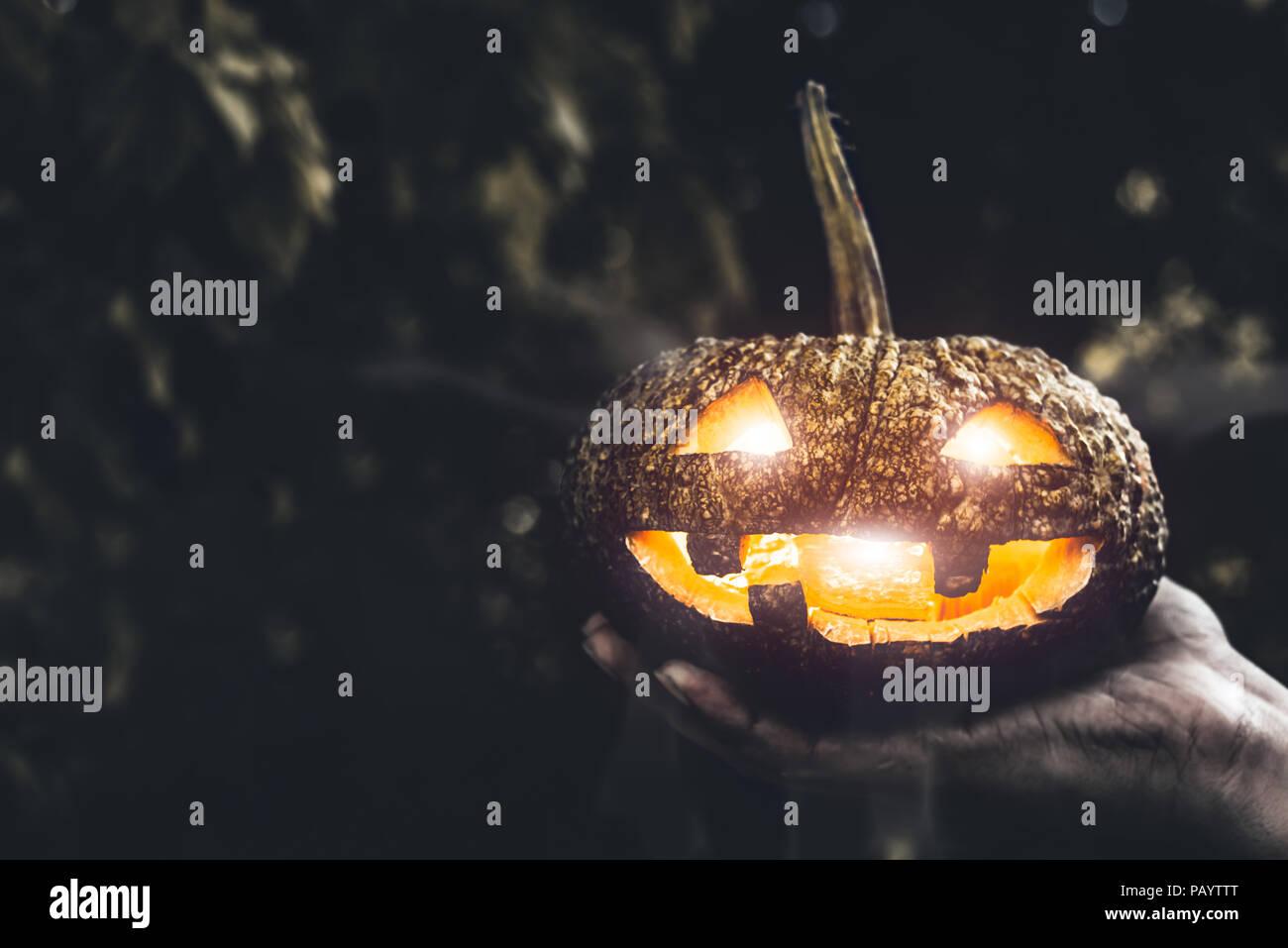 Halloween Kürbis in der Hand, Urlaub und Religion Konzept. Ghost in Kürbis Thema. Hexerei und Mystery buchstabiere Thema. Stockbild