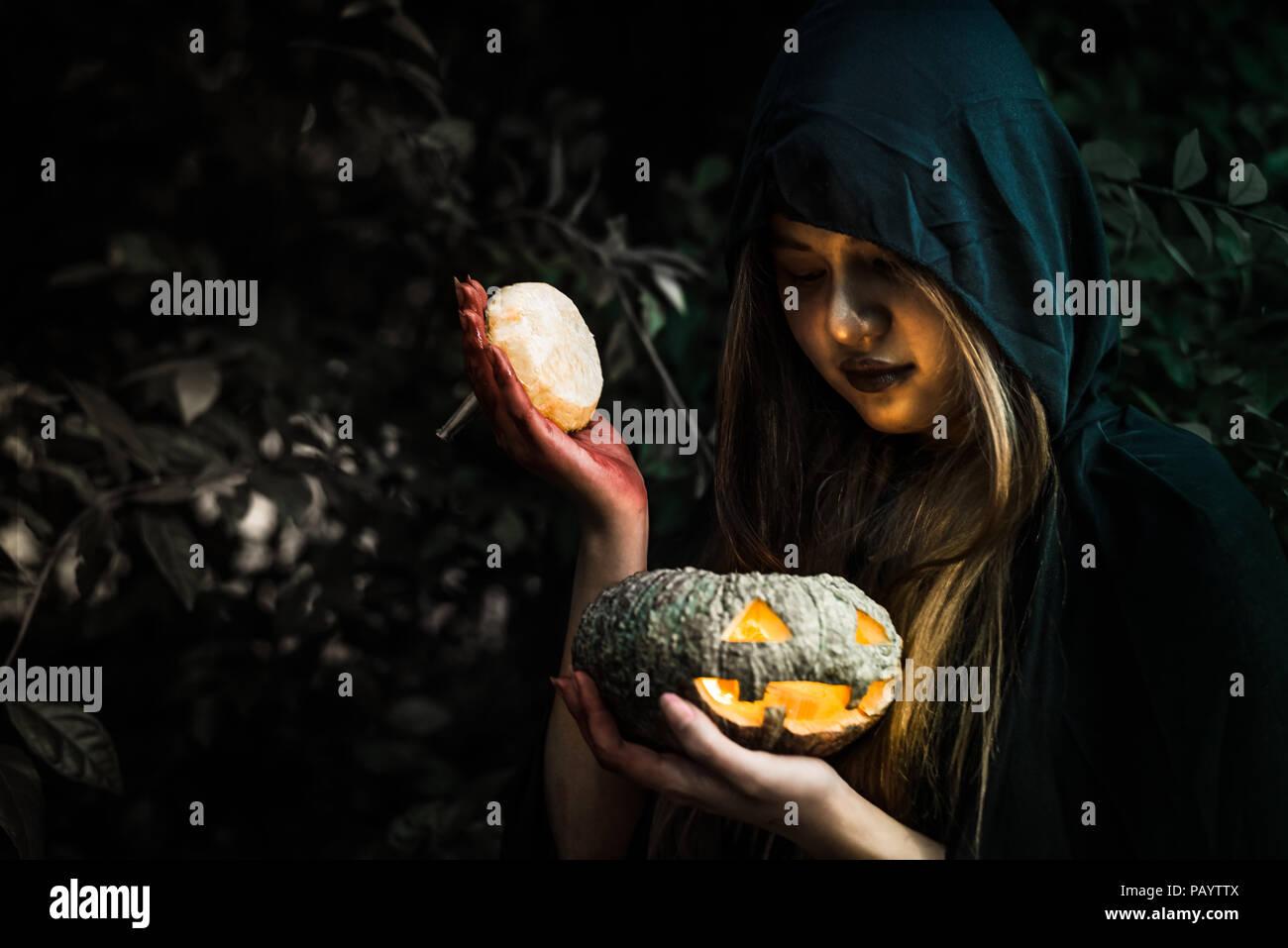 Hexe Eröffnung Kürbis Deckel per Hand. Alte Frau mit hellen Kürbis in den dunklen Wald. Halloween Tag und Geheimnis, das Konzept. Fantasie von Magic Thema. Dämon Ein Stockbild
