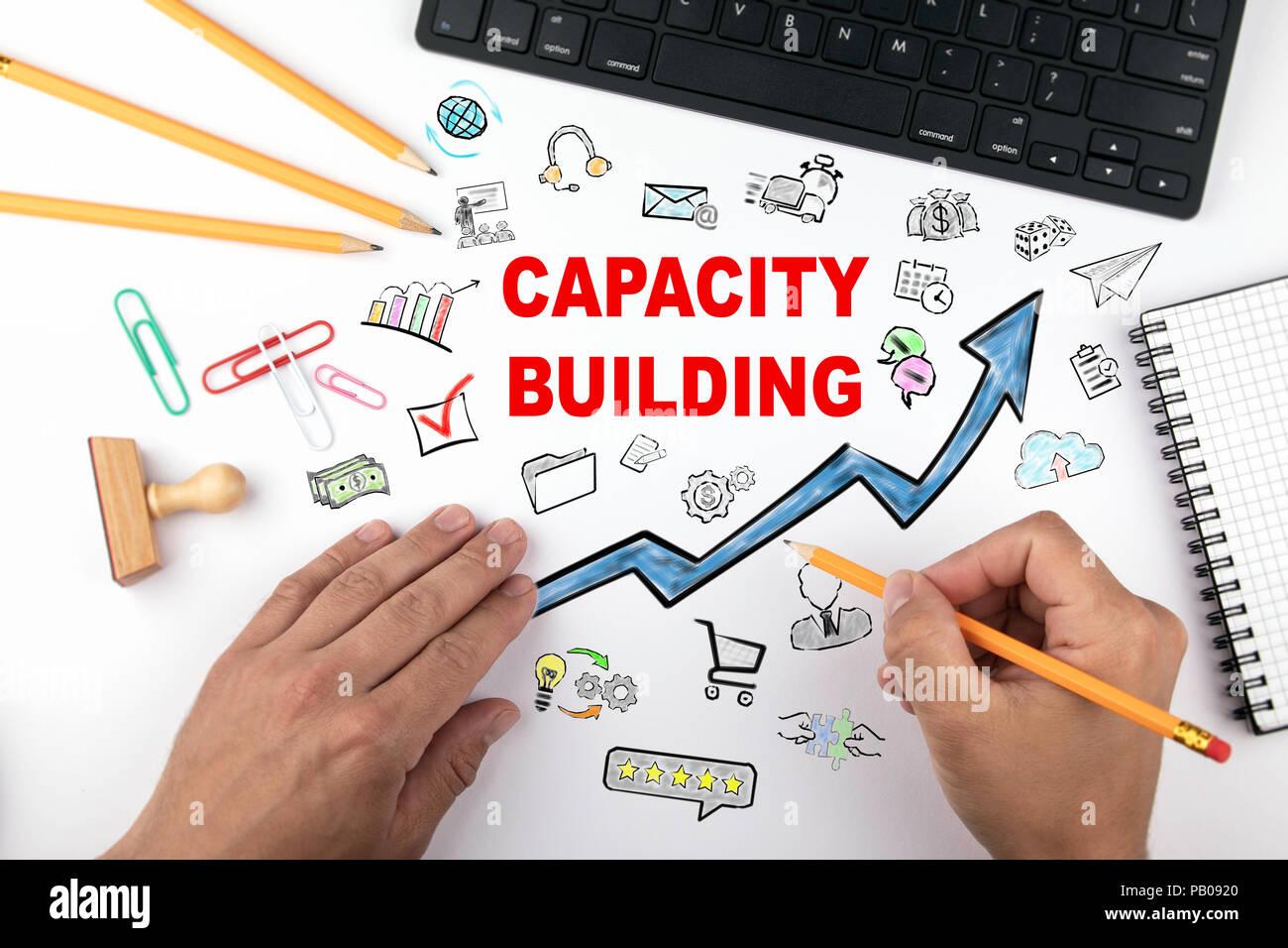 Capacity Building Konzept. Blauer Pfeil und Symbole rund um. Hände auf Schreibtisch Tun des Geschäfts Stockbild