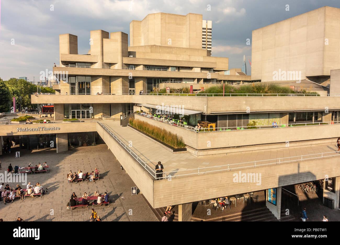 Touristen und Einheimische genießen Sie einen heißen Juli Abend außerhalb der konkreten Brutalist Architektur des National Theatre in London, Großbritannien Stockbild