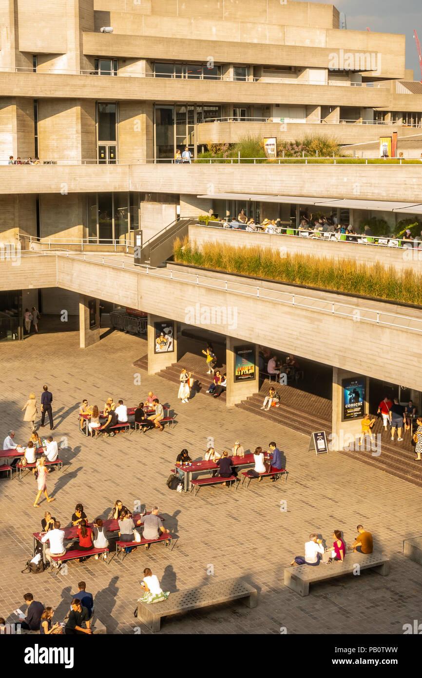 Touristen und Einheimische genießen Sie einen heißen Juli Abend außerhalb der konkreten Brutalist Architektur des National Theatre in London, Großbritannien Stockfoto