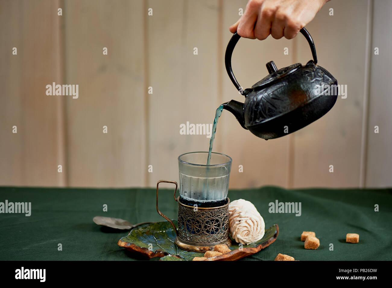 Kaffee mit blauer Tee. Blume Kräutertee. Frauenhände, gießt Kaffee aus dem Wasserkocher in einem Glas mit Becherhalter Stockbild