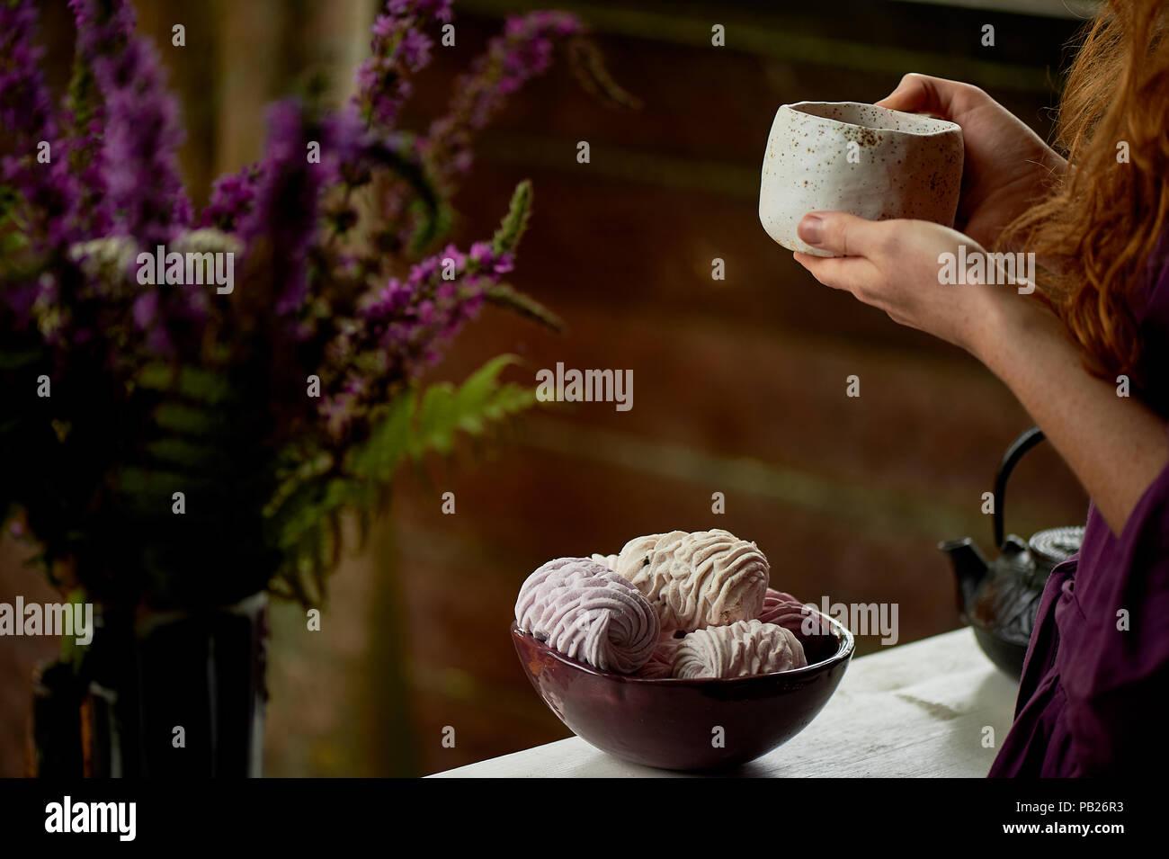 Rothaarige Mädchen in einem lila Kleid mit einem massiven Ton Tasse mit Tee. Tee auf die frische Luft. Genießen Sie das Leben Stockbild