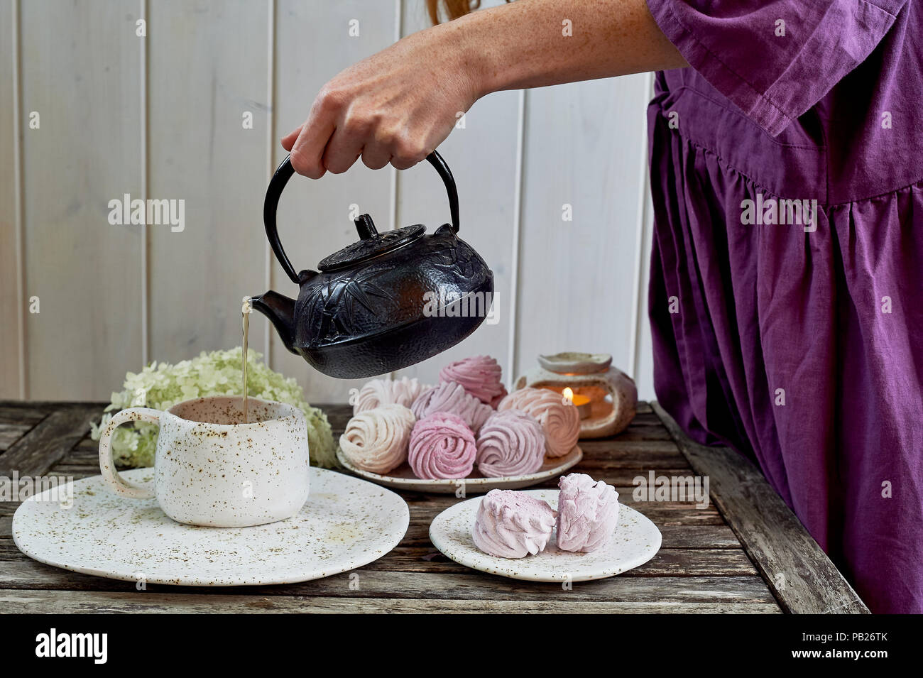 Das rothaarige Mädchen in ein lila Kleid gießt Kaffee in eine Tasse, die Tabelle in die Luft gesetzt ist. Marshmallow. Stockfoto