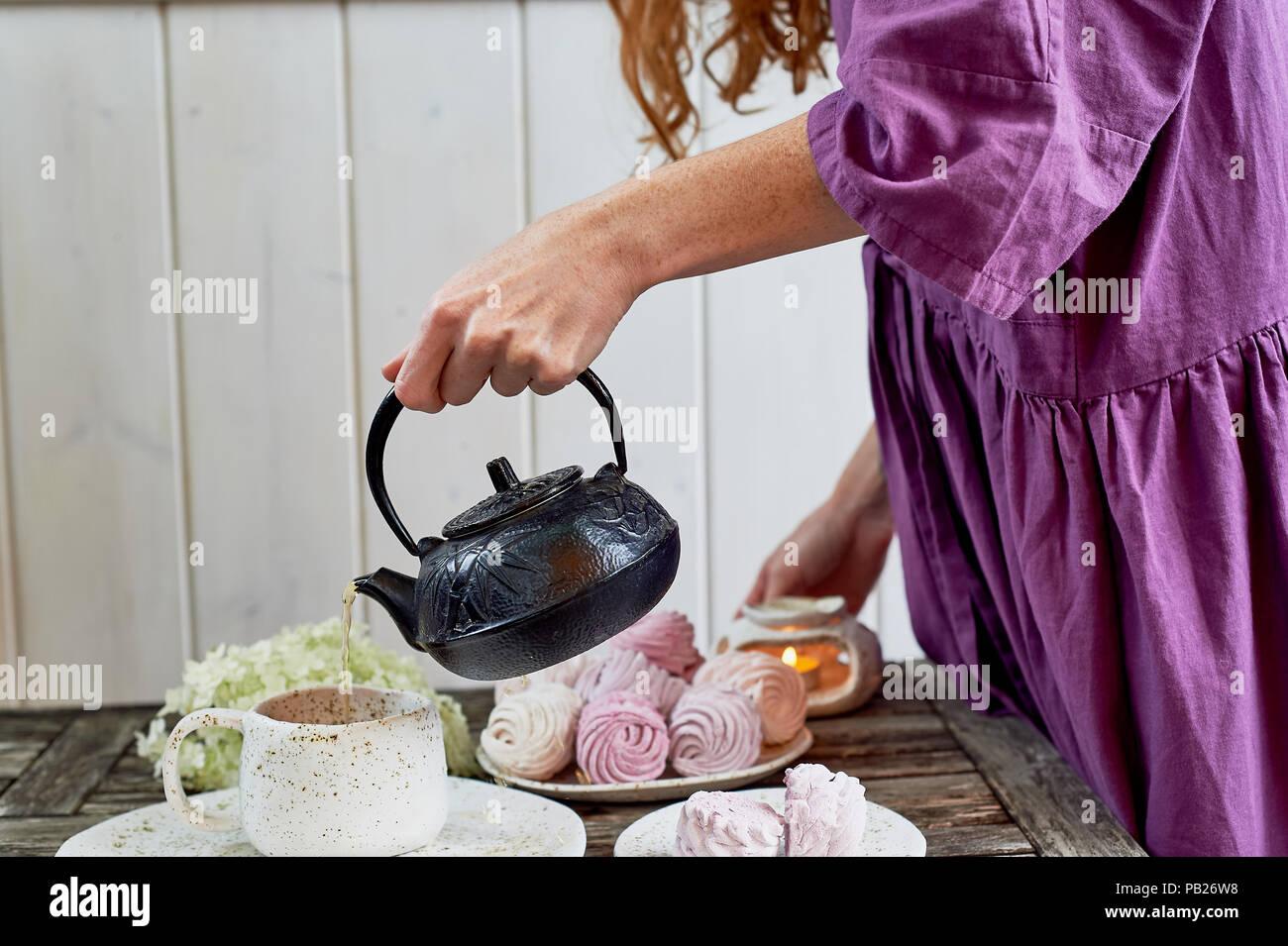 Das rothaarige Mädchen in ein lila Kleid gießt Kaffee in eine Tasse, die Tabelle in die Luft gesetzt ist. Marshmallow. Stockbild