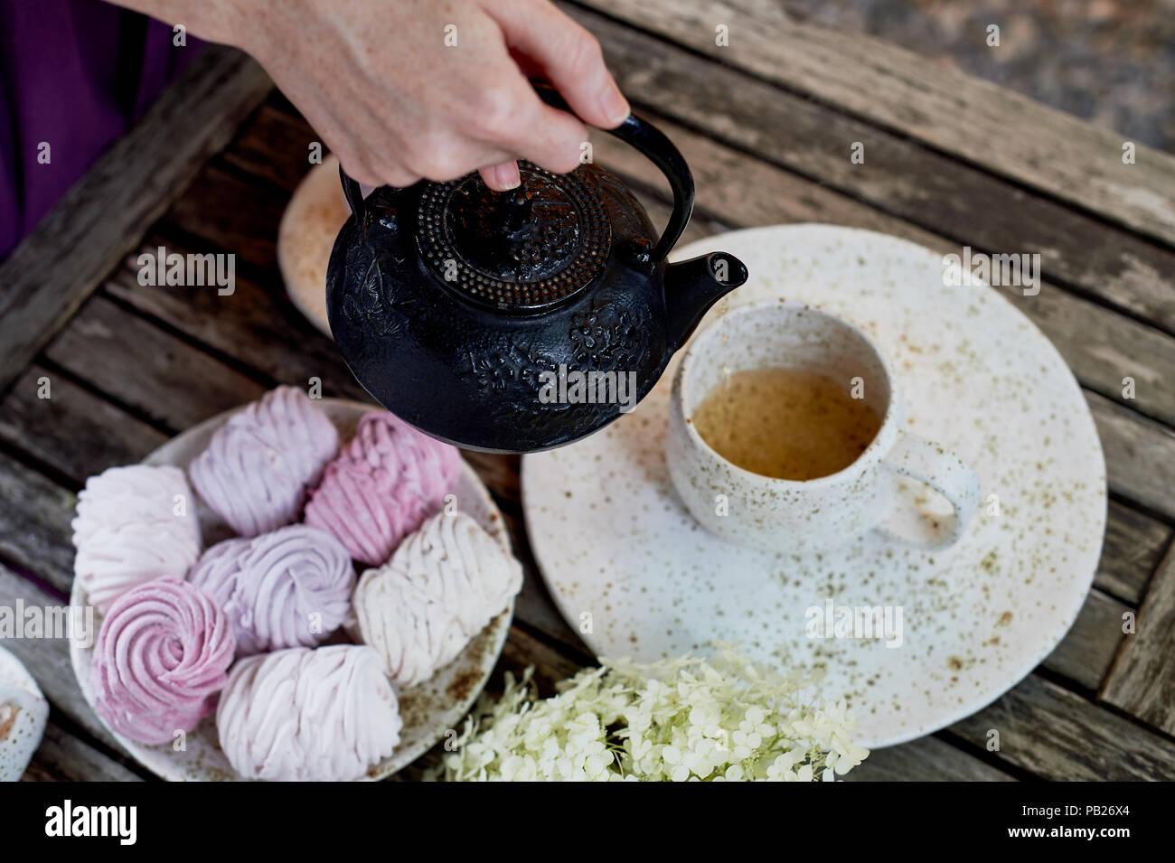 Frauenhände, gießen Kaffee in eine Tasse, die Tabelle ist in der Luft. Marshmallow. Hortensie Stockbild
