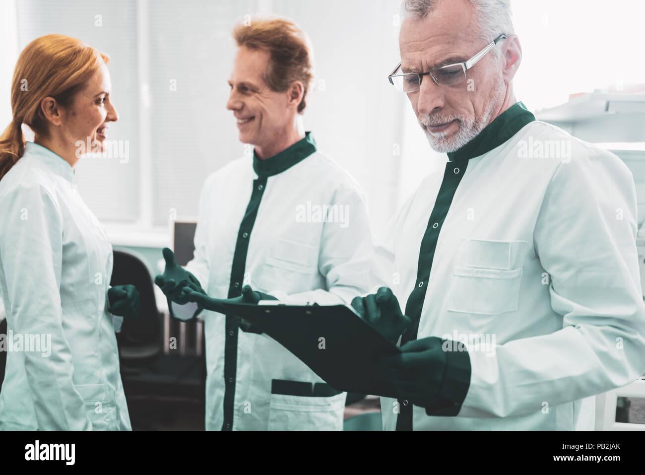 Im Alter von wohlhabenden Chemiker Kontrolle Monatsbericht der Arbeitnehmer Stockfoto