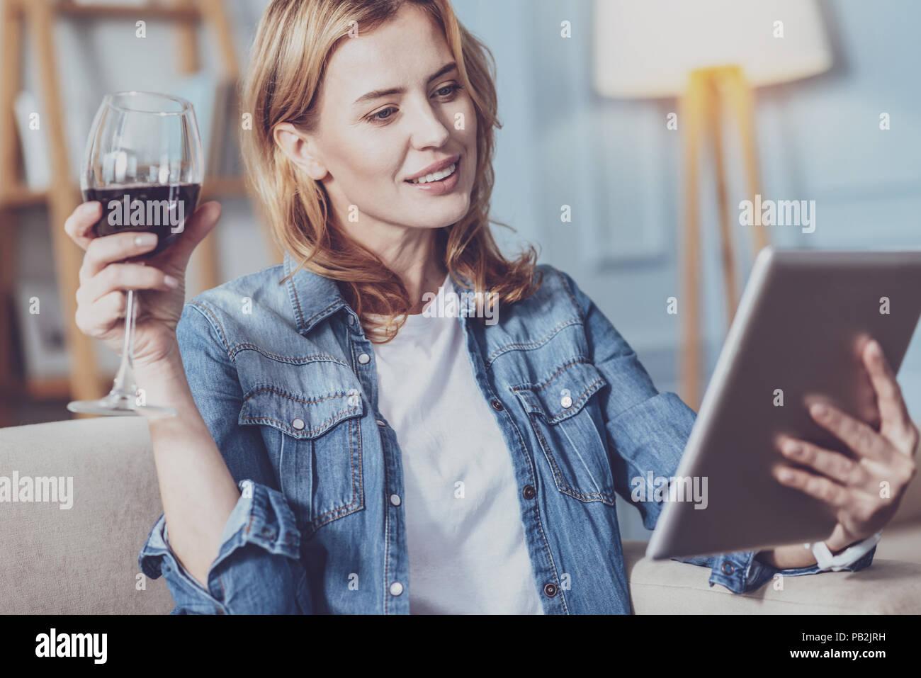 Gerne junge Frau trinkt Wein Stockbild
