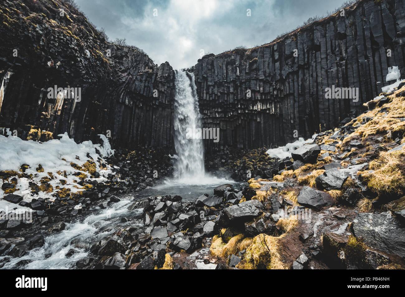 Dramatische morgen Blick auf berühmte Svartifoss (Schwarz) Wasserfall. Farbenfrohe Sommer Sonnenaufgang in Skaftafell, Vatnajökull National Park, Island, Europa. Künstlerischen Stil nachbearbeitete Foto. Stockbild