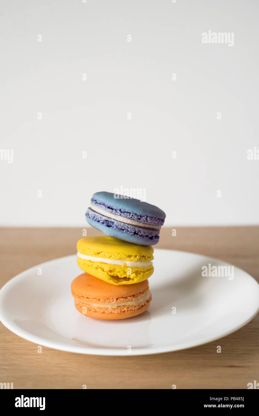 Gekippt Haufen von drei französischen Dessert Trio-Makronen auf einem weißen Teller zu gönnen Sie sich Stockbild