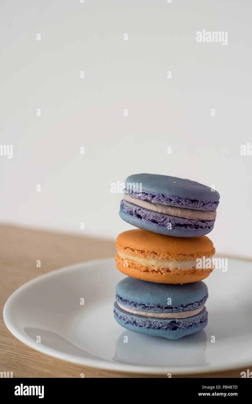 Macaron schiefen Turm in Blau und Orange Sitzen auf einer Platte auf einer hölzernen Zähler vor einem hellen Hintergrund Bereit für Text Stockbild