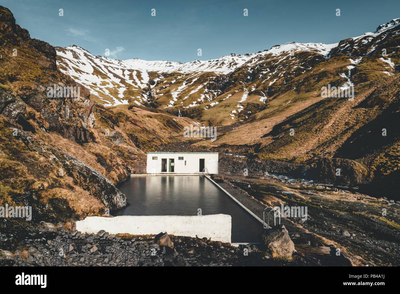 Natürlichen Swimmingpool Seljavallalaug in Island mit Mann in Wasser und Schnee und die Berge rundum. Sonnenschein und blauer Himmel. Stockbild