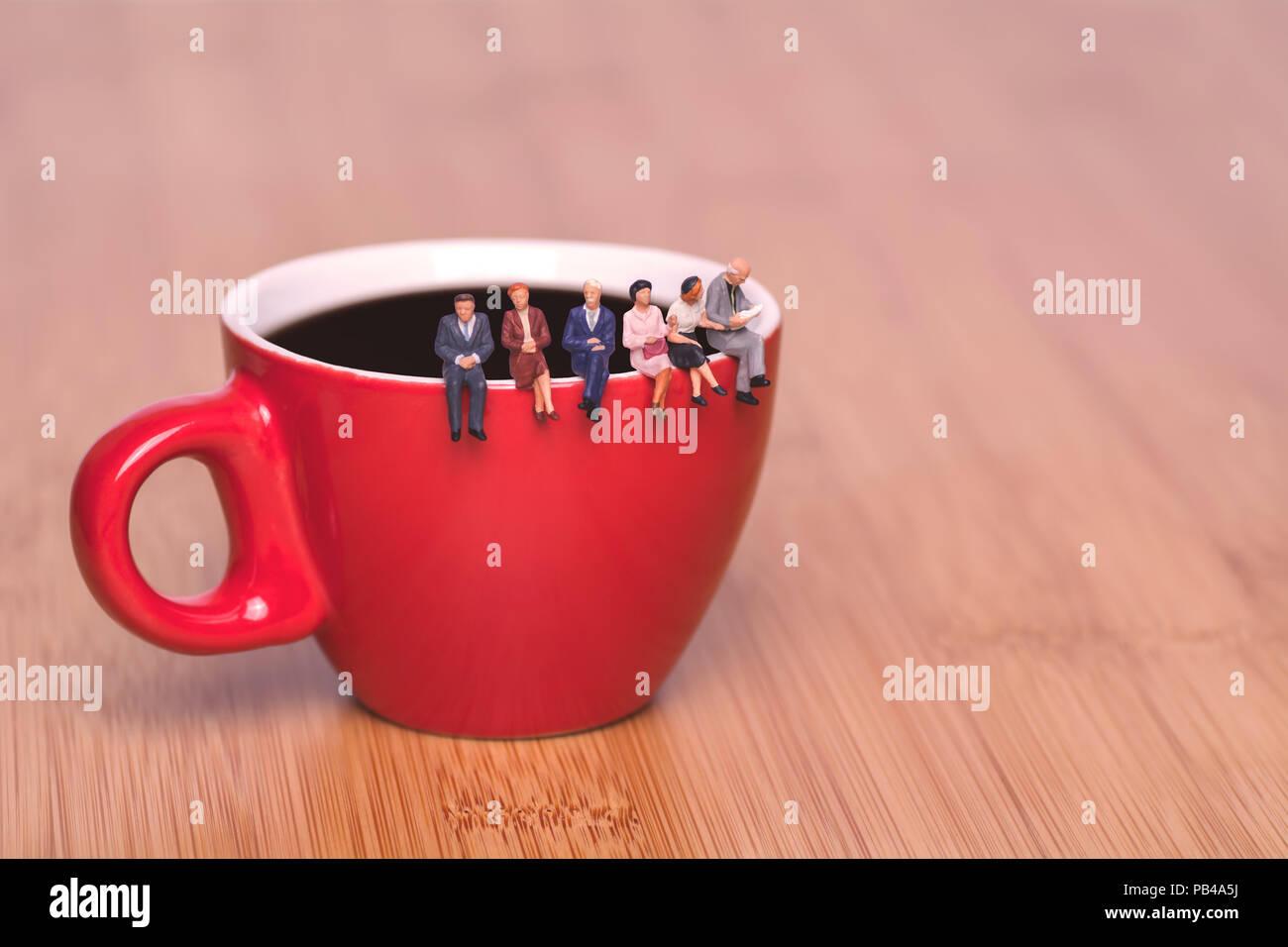 kreatives konzept ber das trinken kaffee und wartet miniatur leute sitzen am rande einer tasse. Black Bedroom Furniture Sets. Home Design Ideas