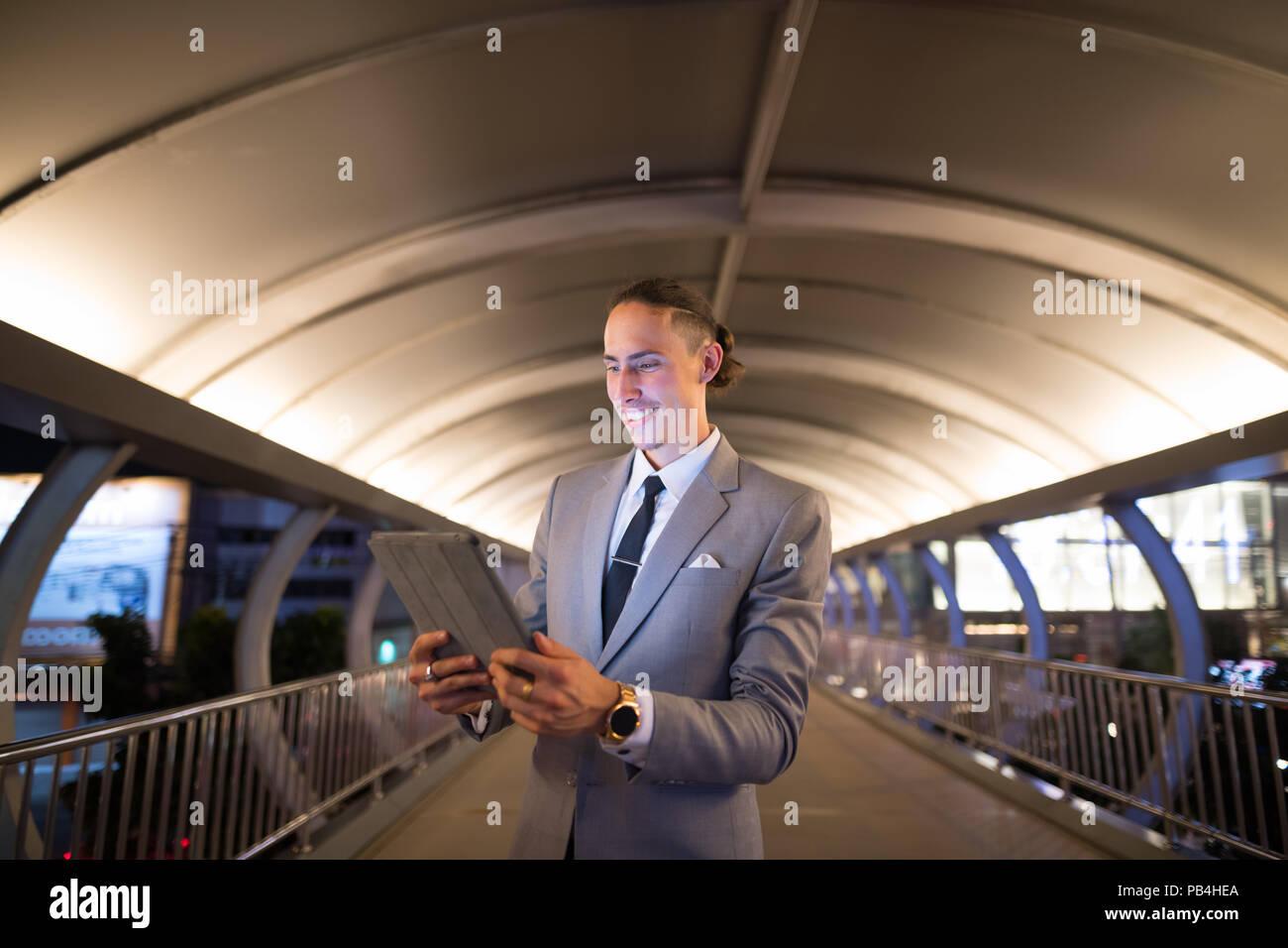 Unternehmer im Freien bei Nacht mit digitalen Tablet Stockbild