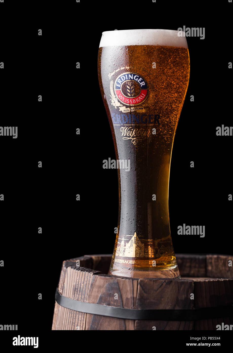 LONDON, Großbritannien - 28 Juli, 2018: Original Glas Erdinger Bier auf Holzfass auf Schwarz. Erdinger ist das Produkt der weltweit größten Weizen Bier Stockbild