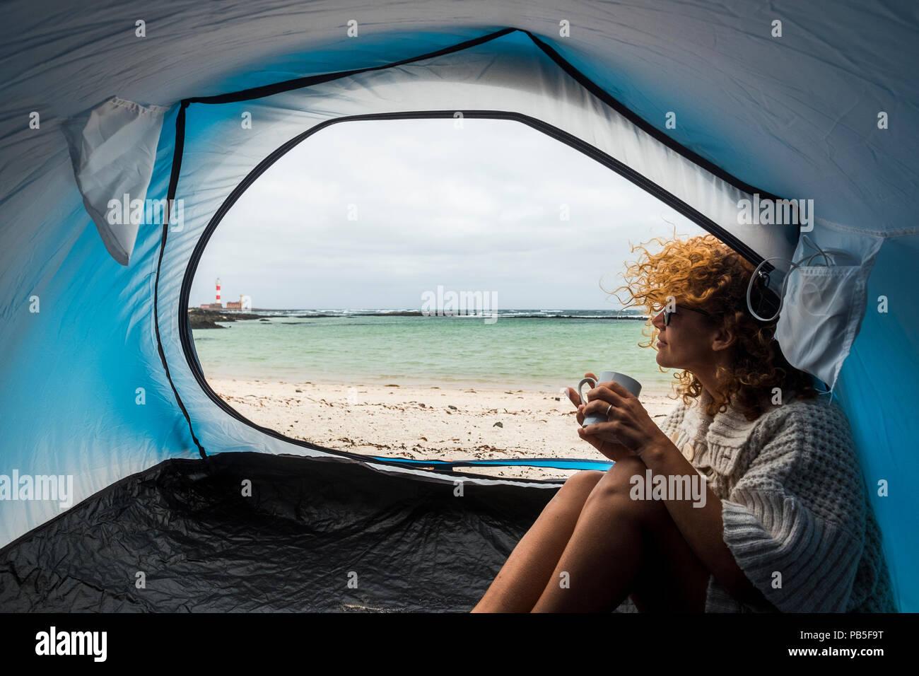 Einsame schöne Frau sitzt auf der Hütte suchen außerhalb. Wind im Haar und Camping am Strand in der Nähe der Farben von Wasser und Land. Freiheit und Stockbild