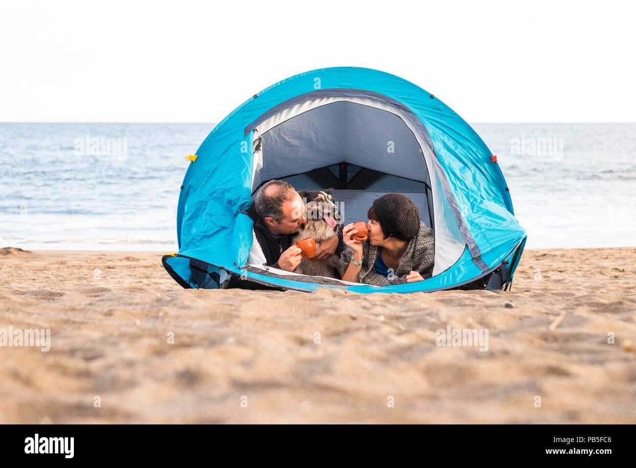 Paar am Smartphone suchen und Spaß haben in einem Zelt im Freien Campingplatz am Strand Hund Border Collie hinter Ihnen in die Kamera schaut. Vintage Stockbild