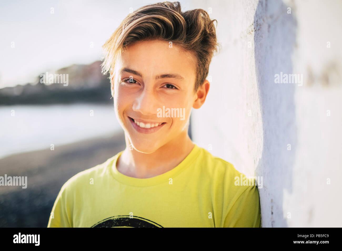 Junge schöne männliche Teenager Lächeln im Freien mit einem blauen Himmel Hintergrund. Sommer style concept Bild Stockbild