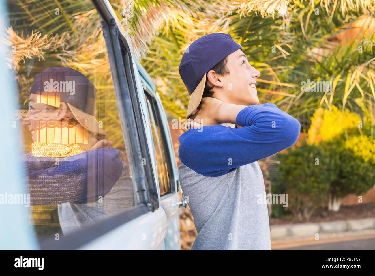 Schönen männlichen Teenager in legerer Kleidung Outdoor Freizeit Aktivität lächelnd und genießen Sie das tropische Wetter. spiegelt sich in einem Jahrgang van Fahrzeug Stockbild