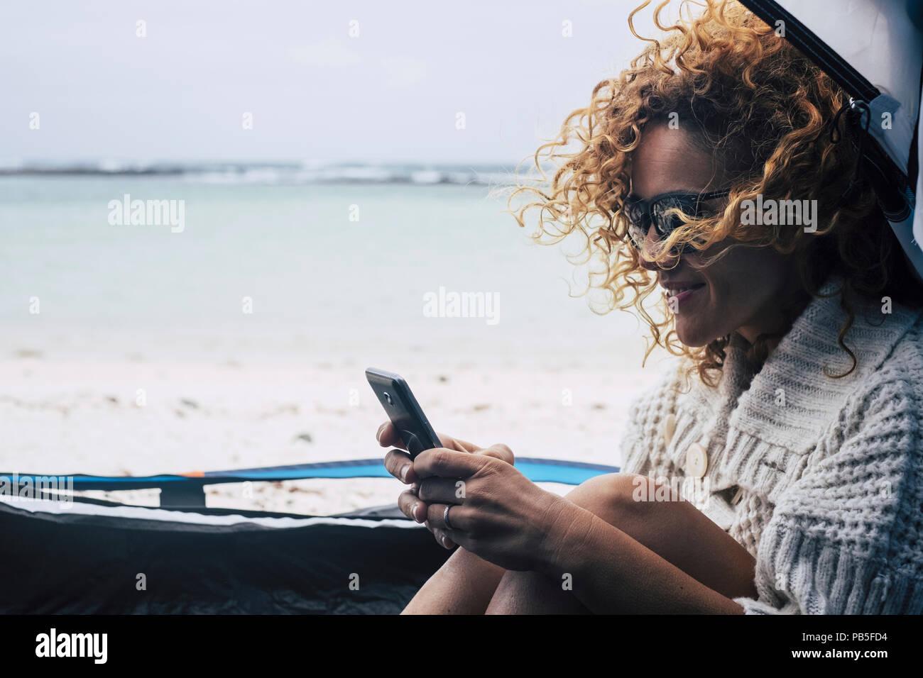 Gut gelaunt Reisende Dame mit gelocktem Haar im Wind auf dem Smartphone enjoyng das Zelt im Freien am Strand schreiben. Blick auf das Meer im Hintergrund. Paradies Ferienhäuser c Stockbild