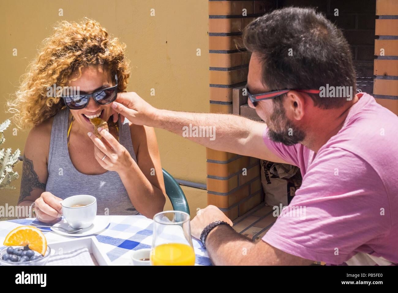 Glückliches Paar von Mann und Frau verheiratet und in Beziehung gemeinsamem Frühstück im sonnigen Morgen zu Hause außerhalb. lächeln und freundlich mit Neigen Stockbild