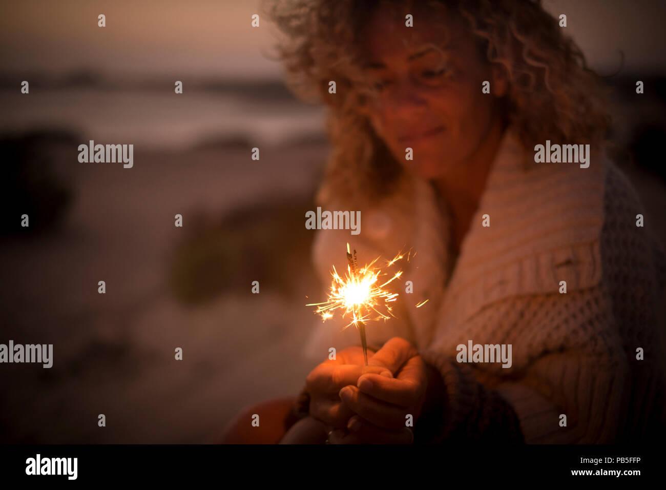 Schöne Dame verwenden und einen funkelnden Feuer Licht in einer Sommernacht. Strand und Meer defokussierten im Hintergrund. Reisen und Ferien Konzept für ein Dre Stockbild