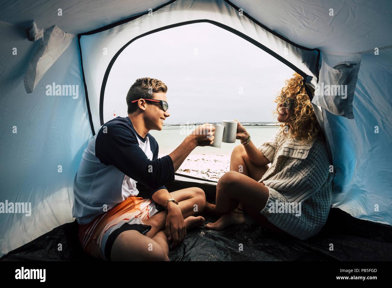 Mutter und Sohn in der Familie Freizeit Outdoor. Reisen und Camping am Strand in der Nähe des Meeres und das Gefühl der Wellen genießen. Trinken einer Tasse Kaffee Stockbild