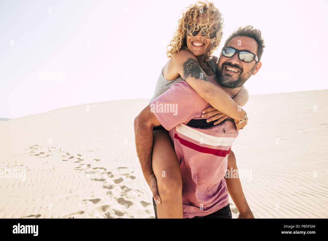 Menschen und Paare, die in Liebe, Spaß haben und die Dünen der Wüste am Strand im Urlaub. Mann tragen auf dem Rücken der Schönen lockiges Haar Frau lächelnd ein Stockbild