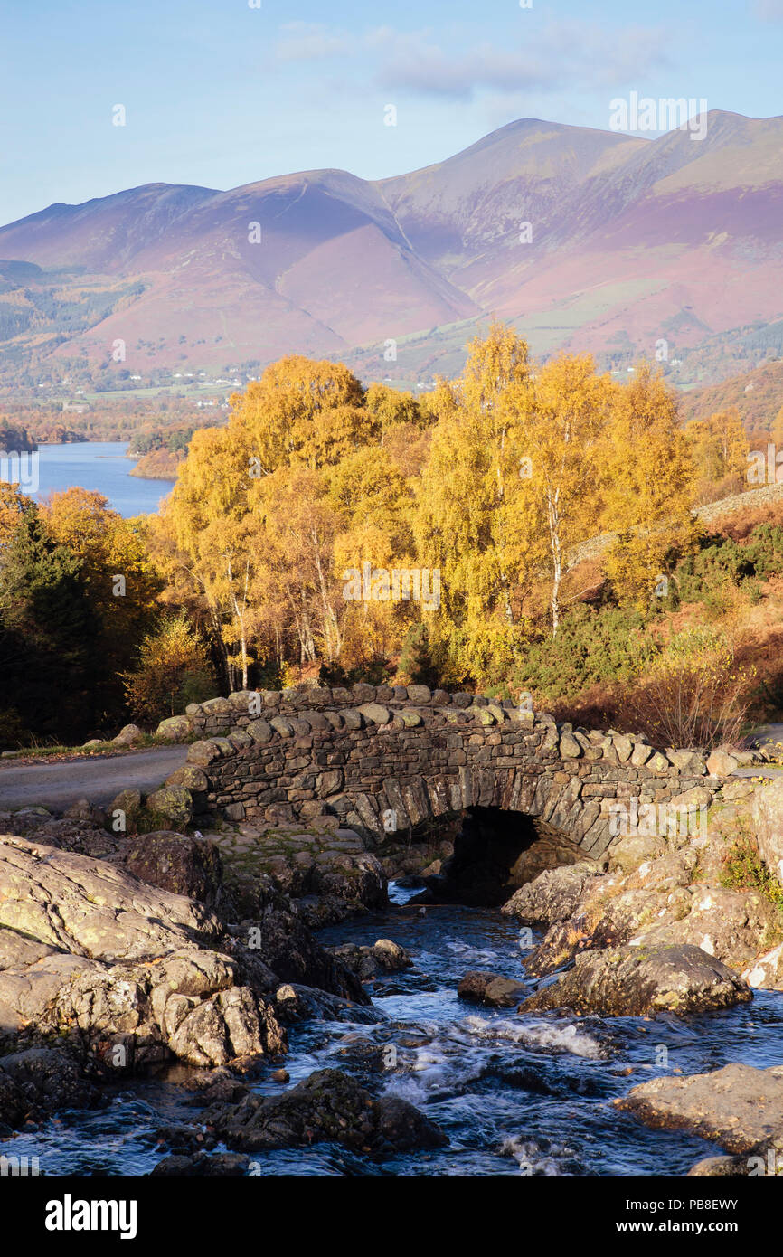Ashness Brücke und Stream mit Bäumen im Herbst, Derwent Water und den Berg Skiddaw jenseits in Lake District National Park. Keswick Cumbria England Großbritannien Stockbild