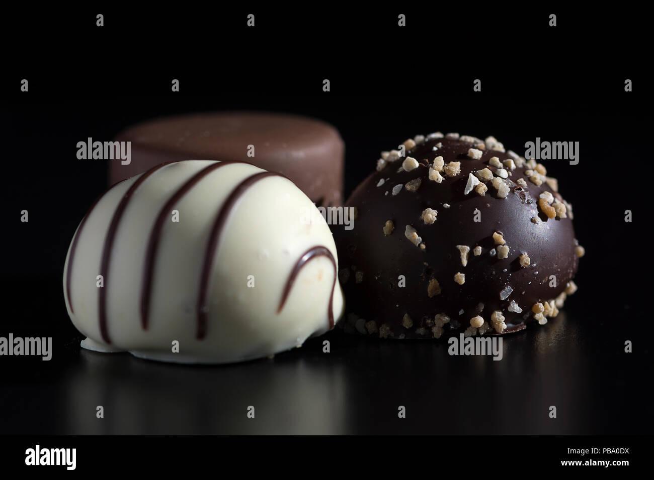 Nahaufnahme von drei Schokolade Bonbons, Weiß, dunkler und Milchschokolade. Süß, Kalorien-reichen und energiereiche Nahrung mit ungesunden und Mast Qualitäten Stockbild