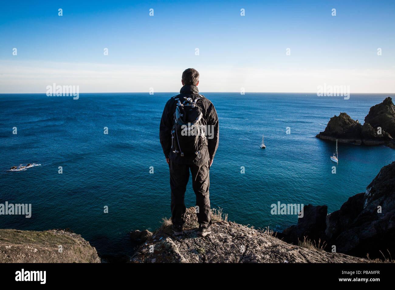 Eine Rückansicht eines männlichen Backpacker oder Wanderer steht auf einer hohen Klippe und bewundern Sie die atemberaubende Meerblick Stockbild