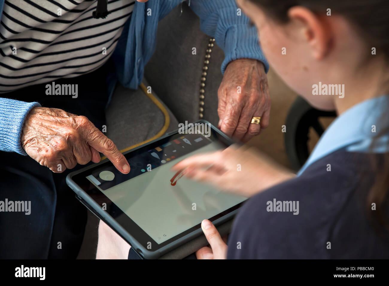 Junge Schulmädchen lehre es Fähigkeiten älterer Bürger auf Tablet über die Schulter pov Stockbild