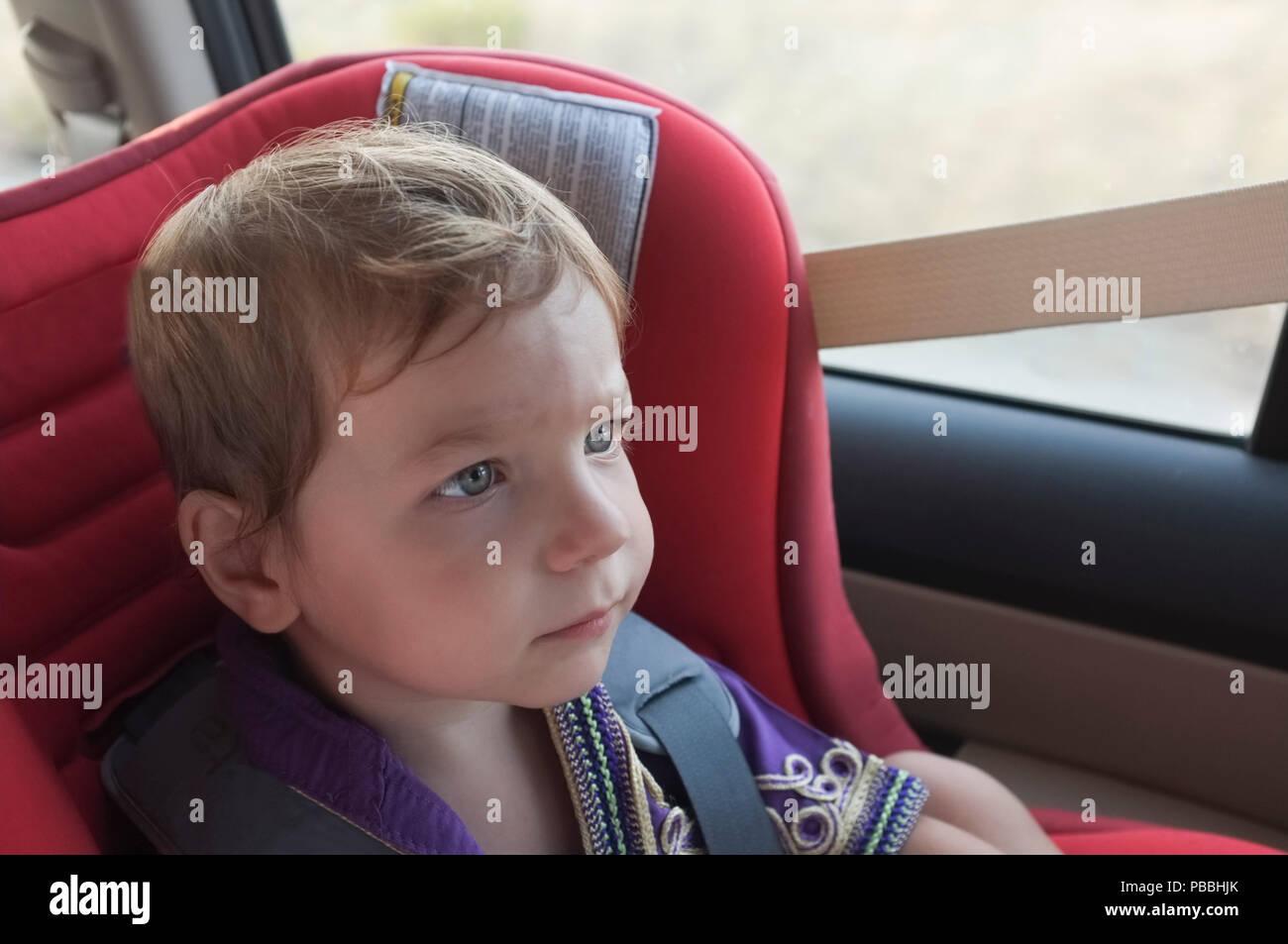 Stattliche aufmerksam baby boy im Kindersitz. Er beobachtet toons mit Tablette auf Kopfstütze Stockbild