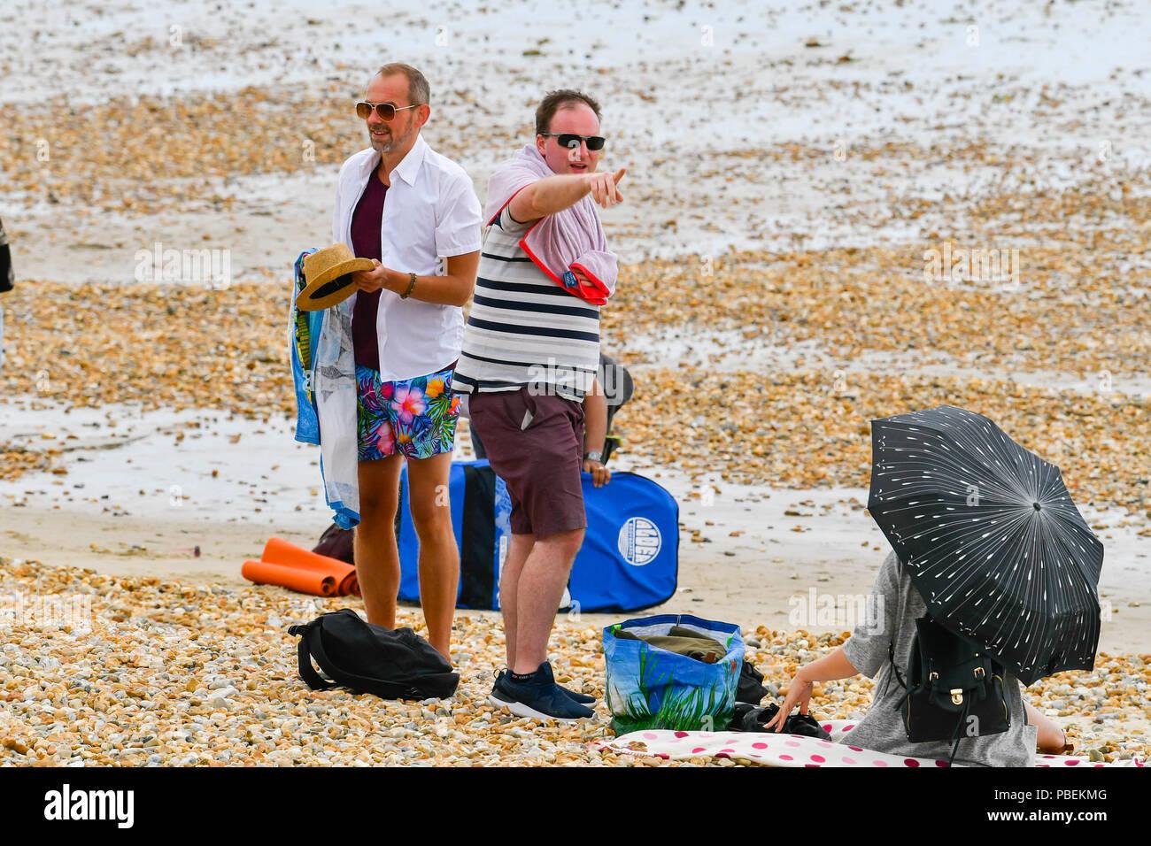 Lyme Regis, Dorset, Großbritannien. 28. Juni 2018. UK Wetter. Urlauber, die Verpackung den Strand zu verlassen, da der Regen beginnt in den Badeort Lyme Regis am ersten Tag der Hauptversammlung der Stadt RNLI lifeboat Woche an einem kühlen, windigen Tag. Foto: Graham Jagd-/Alamy leben Nachrichten Stockbild