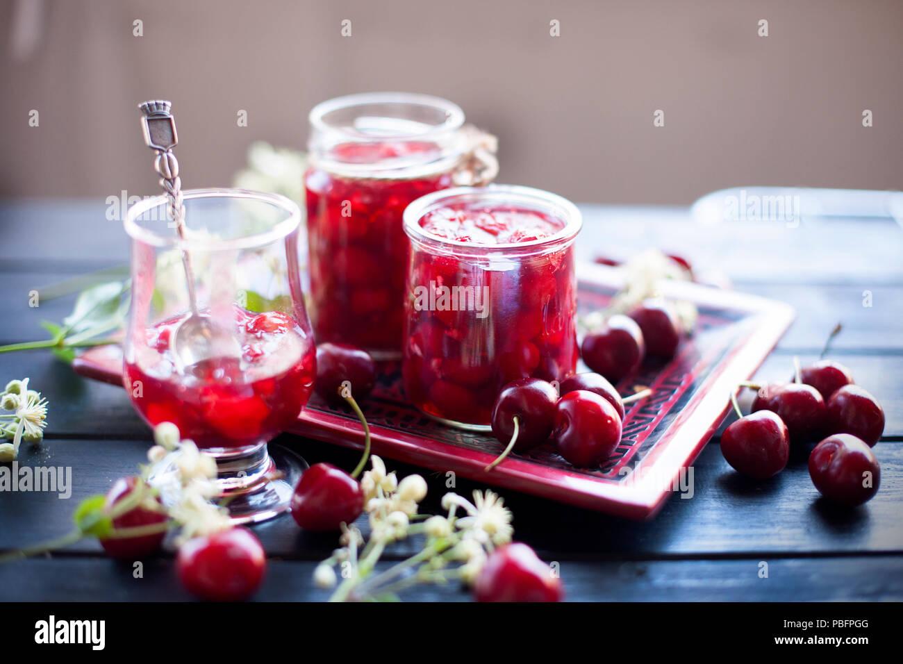 Marmelade aus Kirsche, in Dosen. winter Desserts. Dunkle Foto. Feder weiß blumen Stockbild