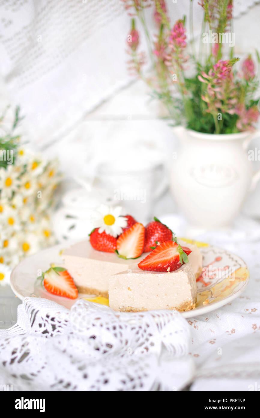 Classic Cheesecake mit Erdbeeren. Auf dem Tisch in der Einrichtung mit Wildblumen und Gänseblümchen. Helle Farben, Stockbild