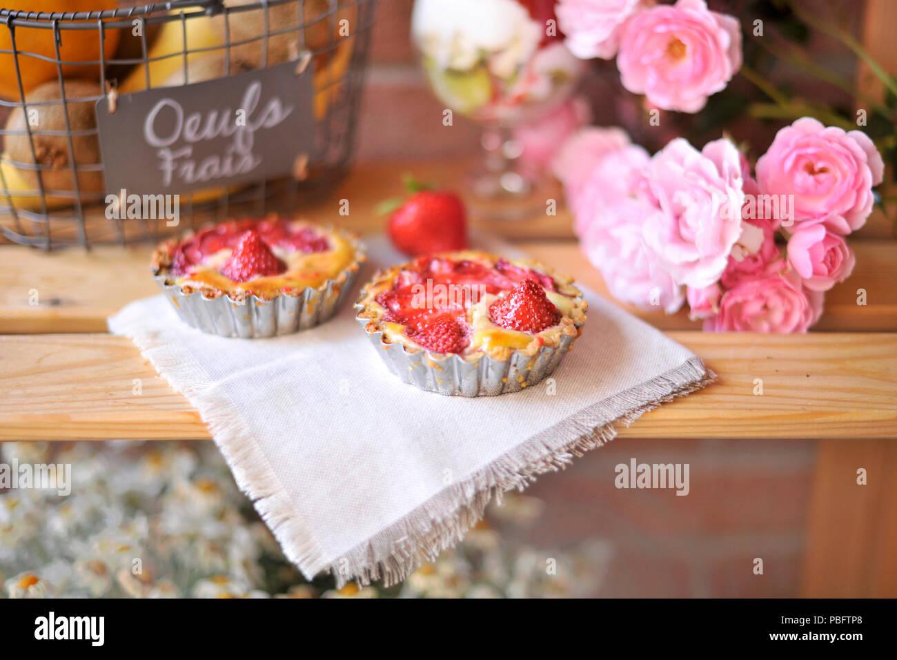 Classic Cheesecake mit Erdbeeren. Auf einem hellen Hintergrund mit einem Strauß Wildblumen in einem jar. Kamille. Einrichtung von Vintage Textilien. Stockbild