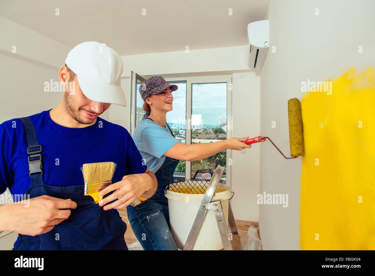 Paar Trägt Blaue Overalls Malerei Ihre Wohnzimmer In Der Farbe Gelb