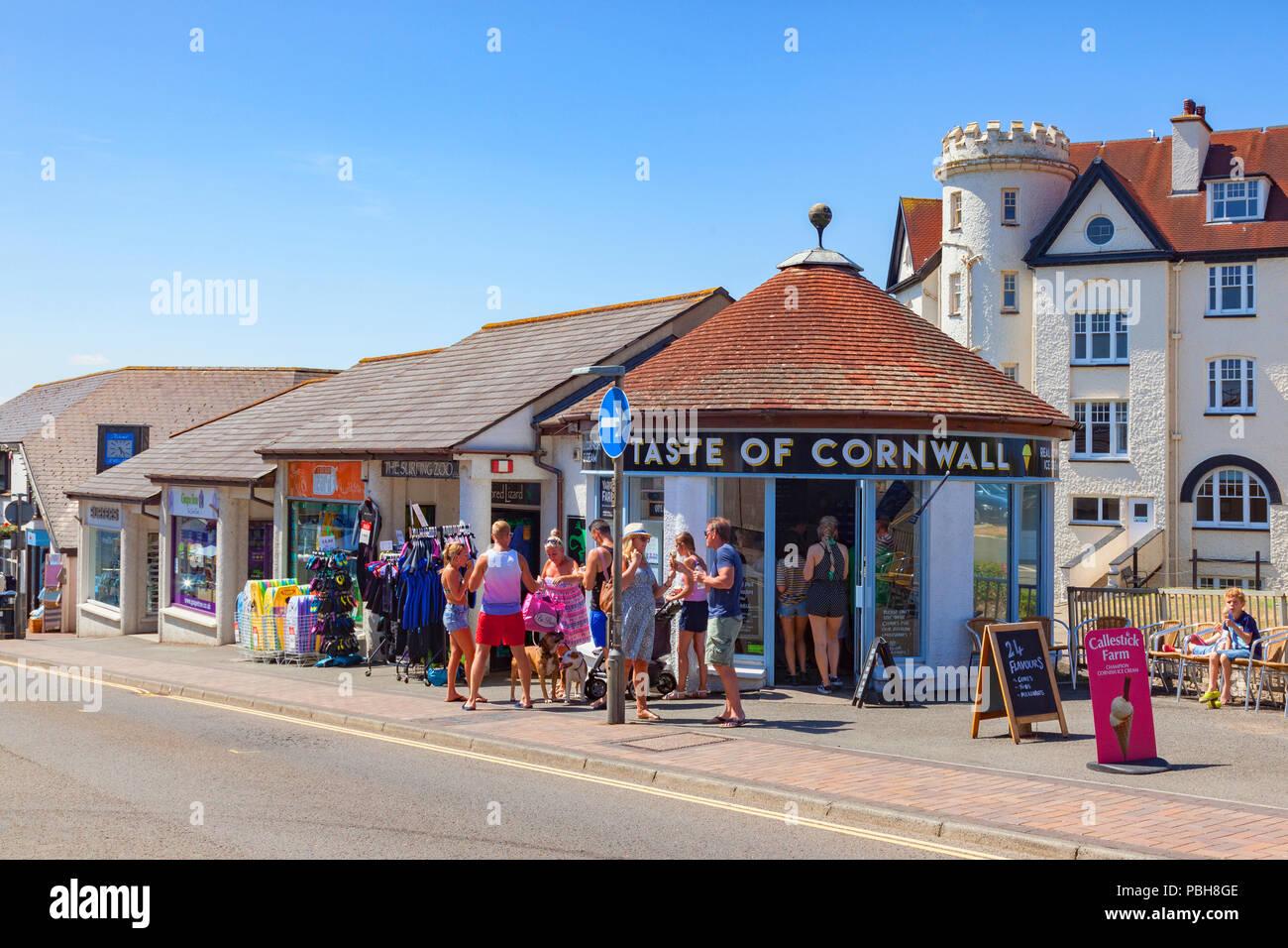 Vom 7. Juli 2018: Bude Cornwall GROSSBRITANNIEN - In der anhaltenden heißen, sonnigen Wetter, Menschen ein erfrischendes Eis essen außerhalb der Geschmack von Cornwall in Belle Anzeigen. Stockbild