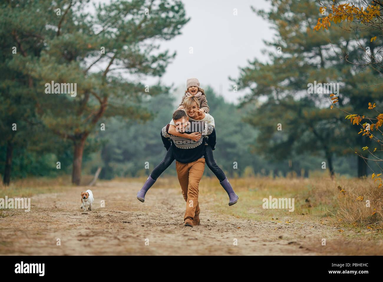 Glückliche Familie hat Spaß und Mann seine Frau und seine Tochter trägt auf seinem Rücken im Wald Weg neben Hund beim Spaziergang im Wald. Stockbild